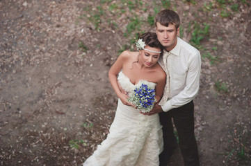 The groom embraces the bride with a wedding bouquet in hands