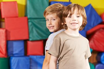 Zwei Jungen Rücken an Rücken in der Turnhalle