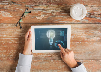 close up of hands with tablet pc and lighting bulb