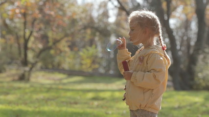 Cute little blonde girl blow bubbles in park