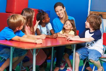 Gruppe Kinder sitzt mit Erzieherin im Kindergarten