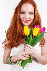 Beautiful redheaded girl is holding yellow and pink tulips