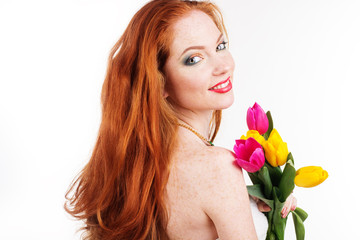 Beautiful redheaded girl is holding tulips isolated on white