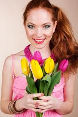 Beautiful redheaded girl is holding tulips