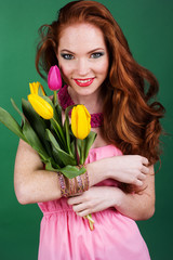 Beautiful redheaded girl with fashion makeup is holding tulips
