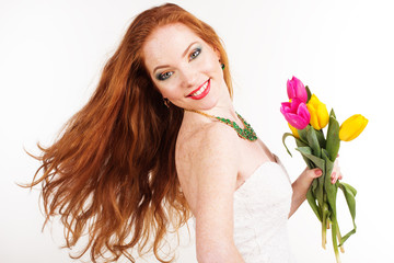 Beautiful redheaded girl is holding tulips