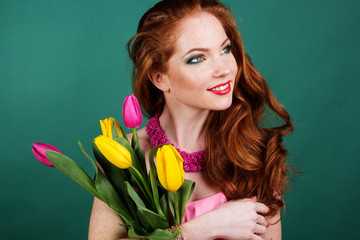 Beautiful redheaded girl is holding tulips, spring