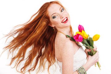 Beautiful redheaded girl with flyong hair and tulips