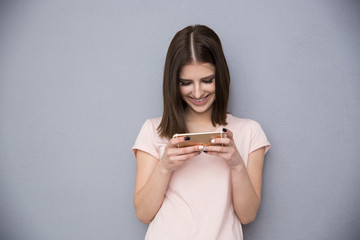 Happy woman using smartphone over gray background