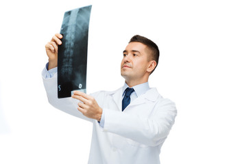 male doctor in white coat looking at x-ray