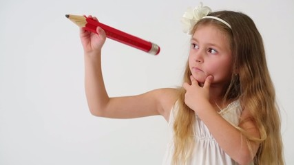 Cute little girl with thoughtful face drawing air big red pencil