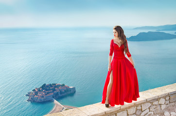 Beautiful Fashion Girl model in gorgeous red dress over the sea,