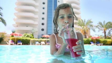 Little pretty girl drinks cocktail in bar in pool near hotel