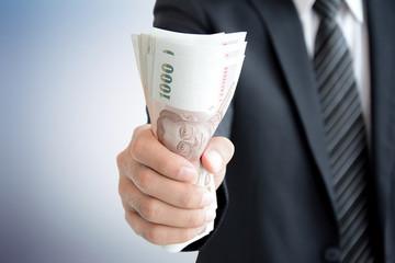 Businessman hand grabbing money - Thai Baht (THB)