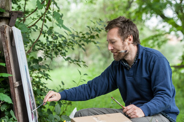 Male artist on painting on canvas in outdoor.