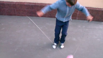 Boy plays with diabolo toy near wall, closeup view in motion