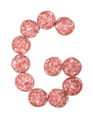 Alphabet letter G arranged from salami sausage slices