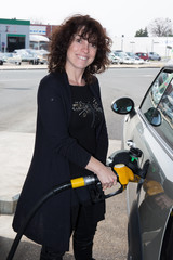 woman refueling her car at the gas station