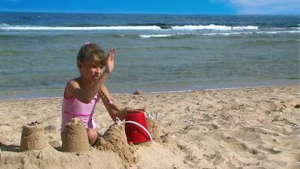 Girls making sandcastles on beach.