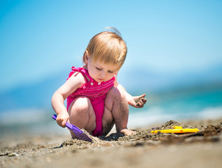 little cute girl playing in the sand