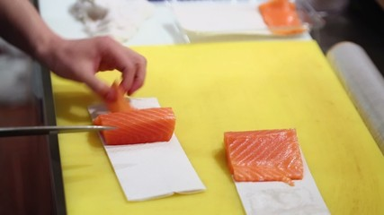 Man cuts fish by slices and puts them in box on table at kitchen