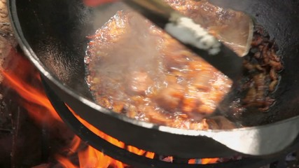 Man mixes broiled onion with meat by colander in pot on campfire