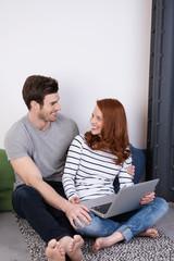 verliebtes paar zuhause mit laptop