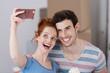 lachendes paar macht ein selfie beim umzug - 80143623