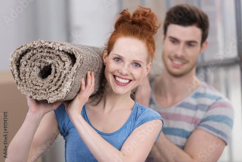 junges paar trägt einen neuen teppich in die wohnung