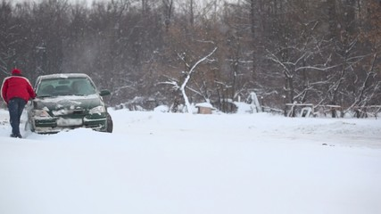 Man and woman tries to release car from snow trap on road