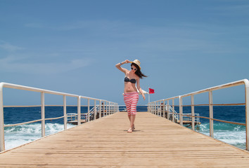 Brunette woman on the pier at the sea.