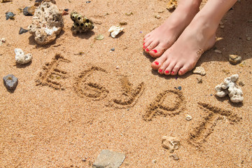 female feet with red pedicure in beach sand with text egypt