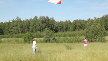 girl holds rope, and guy flies white-orange kite in air