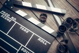 Film. Movie clapper and film reel on a wooden background - 80145491