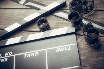 Film. Movie clapper and film reel on a wooden background