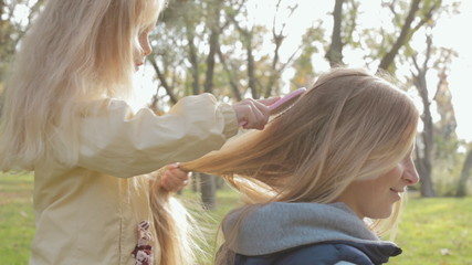 Little girl combing long hair of her mother on nature