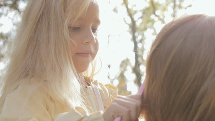 Close up of little girl combing long blond hair of her mother on