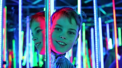 Boy twice emerges from behind corner of mirror labyrinth