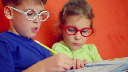 Children in glasses sit together, boy writes by pencil on paper and girl watch