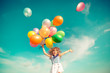 Child jumping with toy balloons in spring field - 80146852