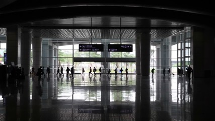 Hall station with columns and silhouettes of hurrying people
