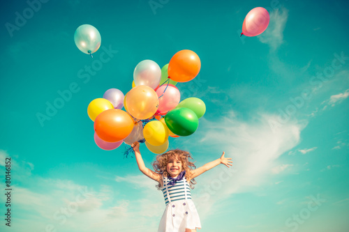 canvas print picture Child jumping with toy balloons in spring field