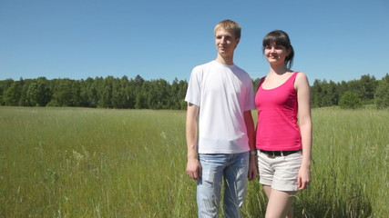 guy with girl stand nearby in field, look and specify afar