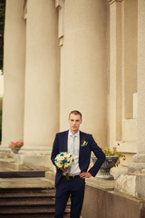 the serious groom with a boquet stands near a stone wall and col