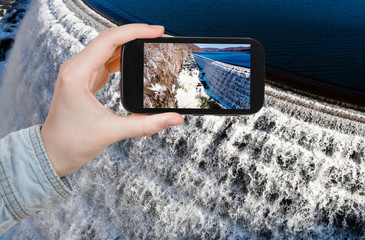 tourist photographs of river waterfall on dam