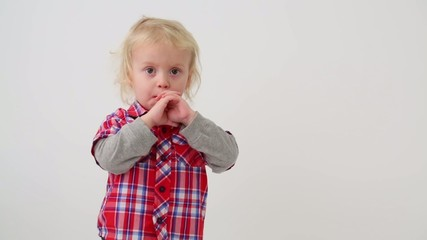 Cute little boy in modern clothes holding hands near the mouth
