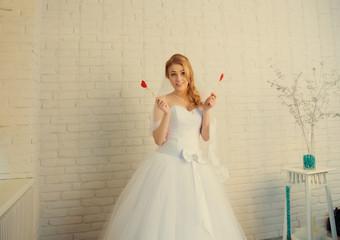 portrait of a happy bride near wall