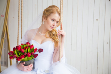Bride on swing holding her red tulip bouquet