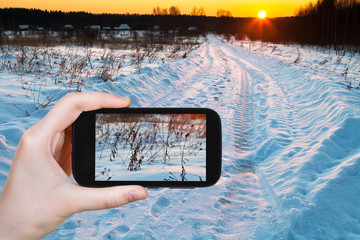 tourist photographs of sunset over snowy field