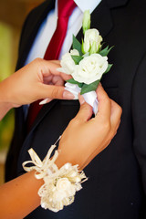 a brides hand putting the boutonniere flower on a groom
